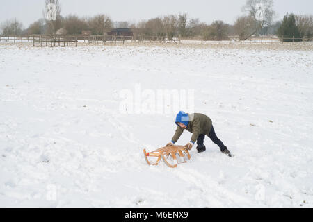 Eight year old boy in the snow using a traditional wooden toboggan or sledge, Medstead, Alton, Hampshire, England, - Stock Photo