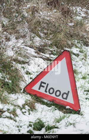 The anomaly of a red flood warning road sign during the snows of the 2018 'Beast from the East'  - in Lostwithiel, - Stock Photo