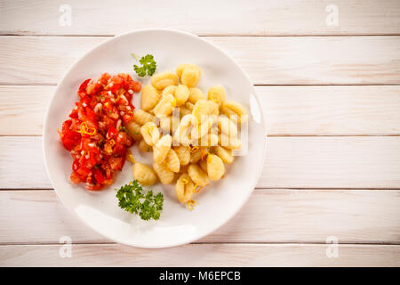 Gnocchi with tomato salad - Stock Photo