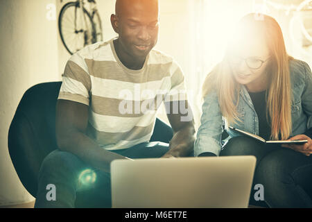 Two diverse colleagues smiling while sitting together working on a laptop in a stylish modern office - Stock Photo