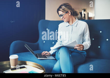 Smiling young businesswoman working online and reading documents while sitting on a sofa in an office - Stock Photo