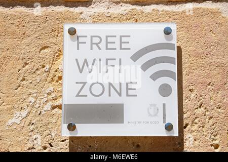 Free Wifi Zone sign on a building wall within the citadel, Victoria (Rabat), Gozo, Malta, Europe. - Stock Photo