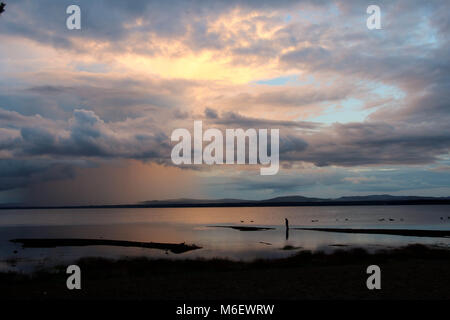 Sunset and clouds reflected in Orsa lake where a person stands on the beach. - Stock Photo