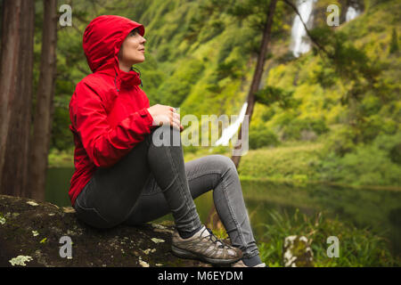 Woman sitting on a stone and enjoying the nature - Stock Photo