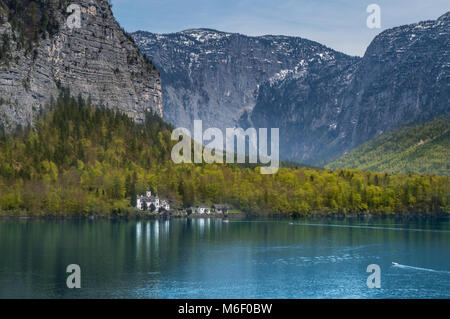 A beautiful castle with mountains in the background on the shores of the pristine Hallstatter lake near Hallstatt - Stock Photo