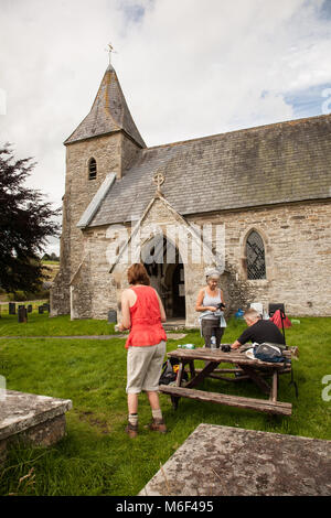 Walkers take advantage of free drinks and biscuits at St Mary's church at Newchurch Montgomery while walking on - Stock Photo