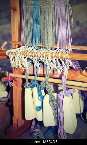 ancient wooden frame for the weaving of woolen threads with heavy stones used as a counterweight with vintage effect - Stock Photo