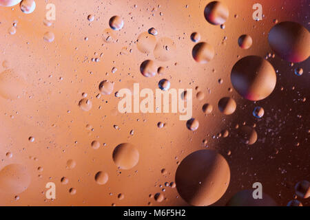 Oil bubbles in an aqueous medium on the border with a glass surface. Abstract Screen Saver. - Stock Photo