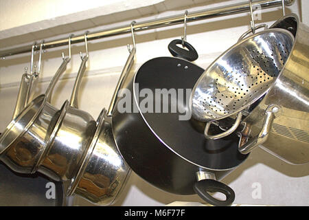 Pots and Pans hanging on a rail in a domestic kitchen - Stock Photo