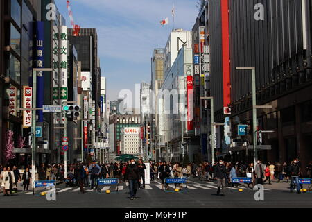 A busy crossing in Ginza in central Tokyo. It's a so-called 'pedestrian paradise day' so some roads are closed to - Stock Photo
