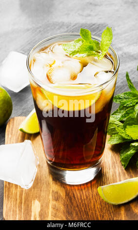 Cocktail Cuba Libre in a glass on a dark background - Stock Photo