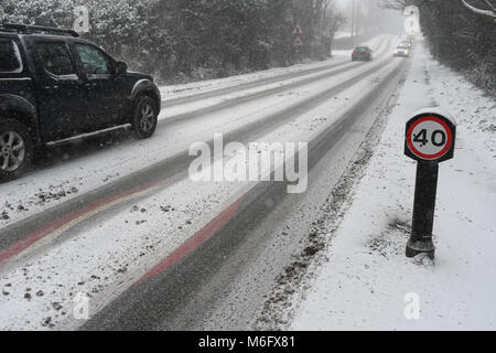 Snow covered 40mph sign on the A36 towards Salisbury England in tricky driving conditions in the snow of March 2018. - Stock Photo