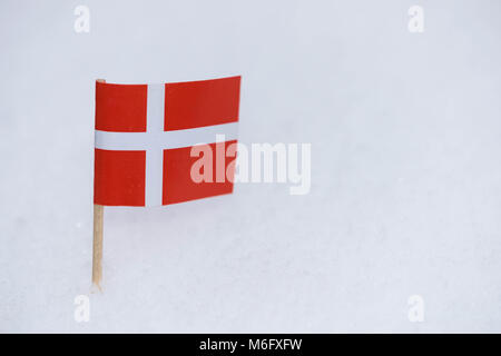 Denmark flag made from paper with brown toothpick on white snow background. - Stock Photo