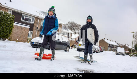 Two boys walk on a snow covered street pulling sledges and body boards to go and play in the March snow and make - Stock Photo