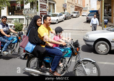 Kashan, Iran - April 27, 2017: Muslim man, his wife in a hijab and their little daughter are riding a motorcycle. - Stock Photo