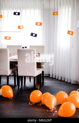 Kids birthday party Photography theme. Orange and black decorations with paper-cut photo cameras and balloons. - Stock Photo