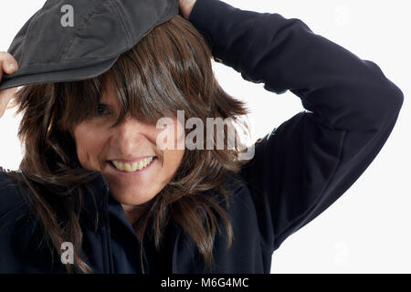 Attractive Middle aged woman with brown layered hair smiling while putting on a driving cap isolated on white - Stock Photo