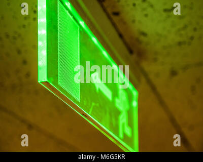 Indoor view green emergency fire exit sign on ceiling. - Stock Photo