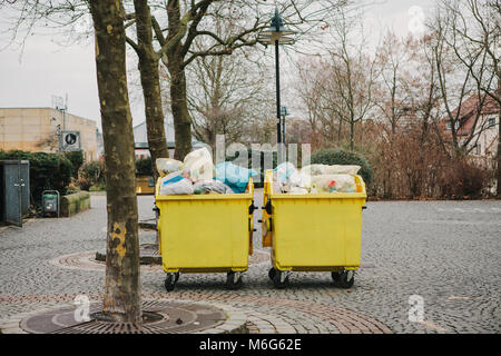 Two yellow garbage containers on a street in Germany. Collection and disposal of domestic waste. - Stock Photo