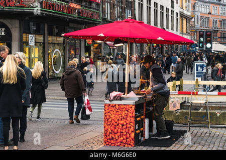 Copenhagen - October 17, 2016: On Nygade Street, a street merchant is frying some nuts for selling those and tourists - Stock Photo