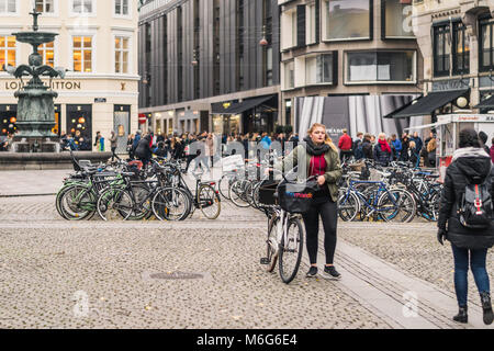 Copenhagen - October 17, 2016: Girls passing by the Local bicycle parking spot in the Amargertorv square. - Stock Photo