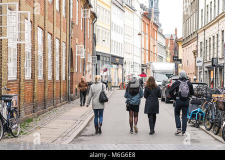 Copenhagen - October 17, 2016: Some passers by on Krystalgade street with a lot of bicycles parked nearby. - Stock Photo