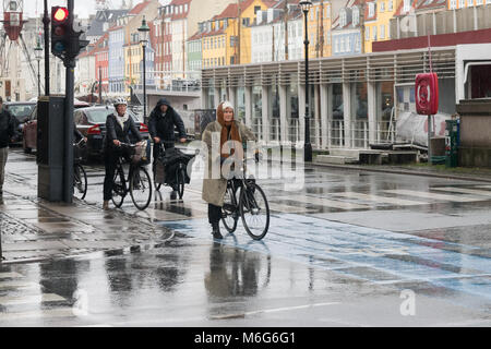Copenhagen - October 23, 2016: An old lady and other people on their bycicles waiting to cross the street during - Stock Photo