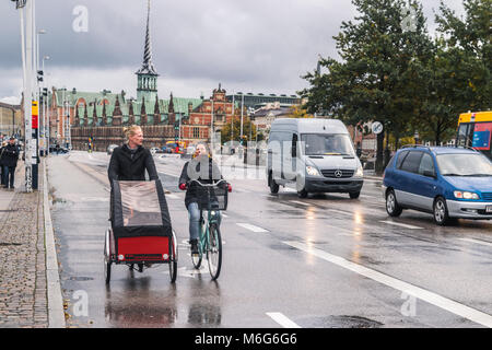 Copenhagen - October 23, 2016: People on their bikes during a rain, smiling. - Stock Photo