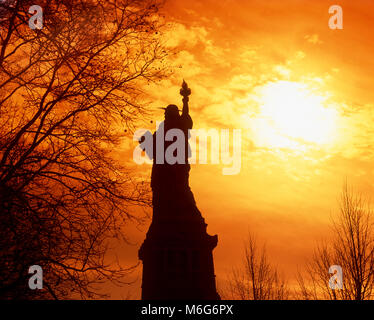 Silhouette of the Statue of Liberty at sunset, New York, USA - Stock Photo