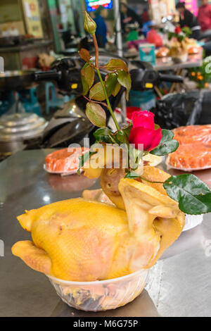 A chicken carcase with a red rose stuck down its throat on a table outside a restaurant in Hanoi, Vietnam - Stock Photo