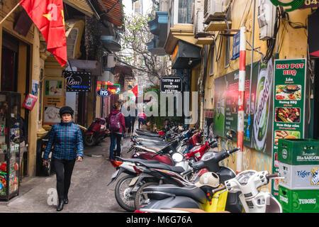 Scooters parked along a narrow street in Hanoi, Vietnam - Stock Photo
