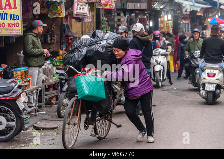 A woman pushes her bicycle loaded with heavy black bags in Hanoi, Vietnam - Stock Photo