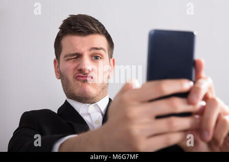 Close-up Of A Young Businessman Taking Selfie With Mobile Phone - Stock Photo
