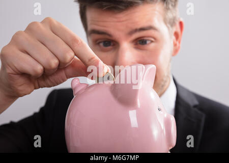 Close-up Of A Businessman Inserting Coin In Pink Piggybank - Stock Photo
