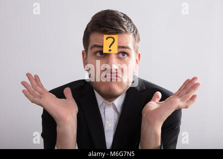 Close-up Of A Young Businessman With Sticky Notes On His Forehead Showing Question Mark Sign - Stock Photo
