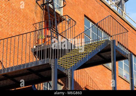 Fire escape staircase on side of industrial brick building, London, England, United Kingdom, UK - Stock Photo