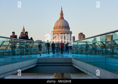 People on the Millennium Bridge with St Paul's Cathedral in the background, London England United Kingdom UK