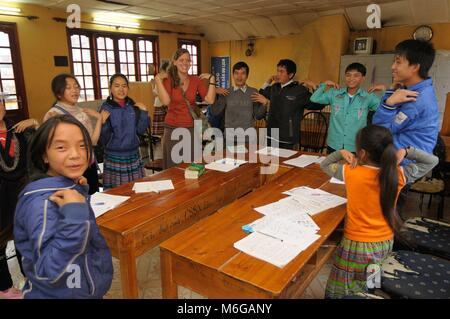 English language classroom in small school in Sapa Vietnam with young female teacher leading a group of Vietnamese - Stock Photo