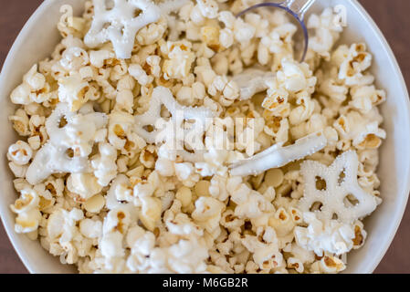 overhead closeup of winter themed popcorn with white chocolate pretzels in bowl - Stock Photo