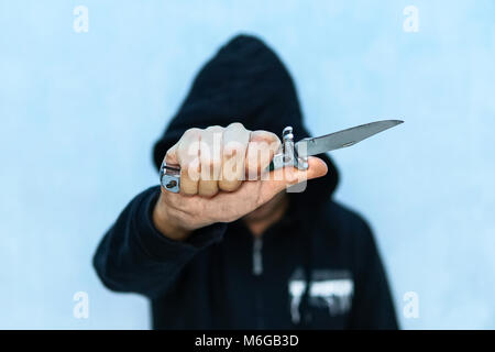A young man in a hoodie holding a knife symbolizing youth crime. Crime concept. The threat of a cold weapon. A terrorist - Stock Photo