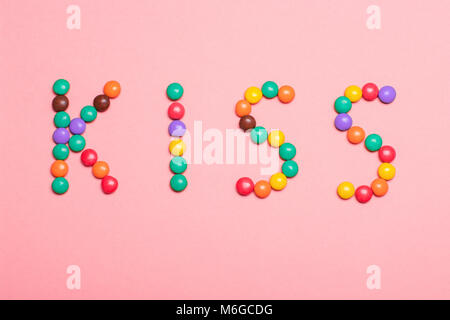 The word KISS is written by sweet colorful chocolate candy on pink background. - Stock Photo