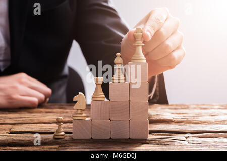 Close-up Of A Businessperson's Hand Arranging Chess Piece On Wooden Blocks - Stock Photo