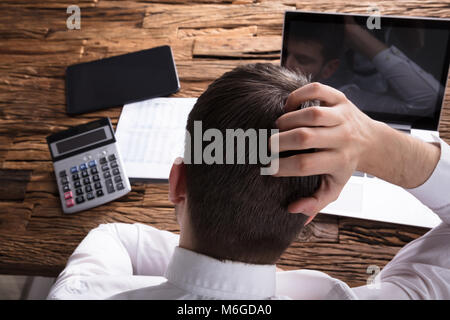 Rear View Of A Stressed Businessman Scratching Head In Front Of Laptop - Stock Photo