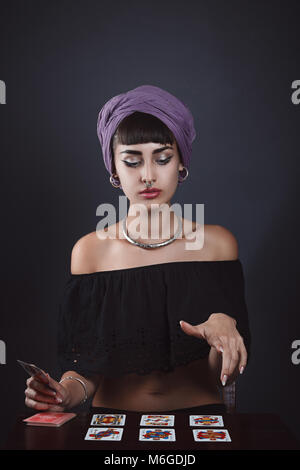 Beautiful fortune teller reading cards. Studio portrait - Stock Photo