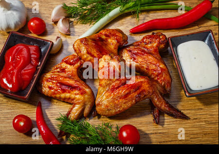 Fried chicken wings and vegetables on a wooden background - Stock Photo