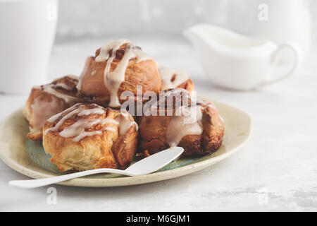 Homemade cinnamon buns in glaze on a light plate, light background, copy space, top view. - Stock Photo