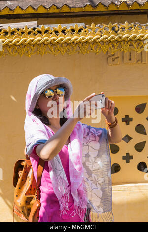 Visitor taking photos with reflections in sunglasses at Shwezigon Pagoda, Nyaung U, Bagan, Myanmar (Burma), Asia - Stock Photo