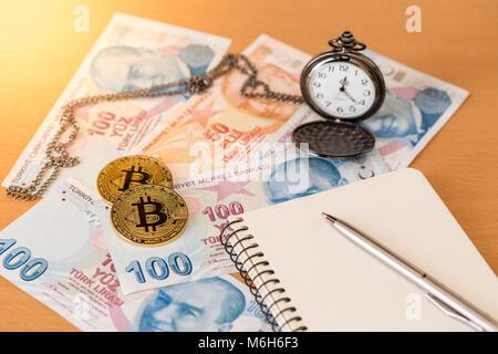 Journal, pen, pocket watch, and two golden bitcoins on turkish liras - Stock Photo