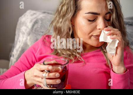 Young sick woman lying in bed with high fever. She is blowing nose - Stock Photo