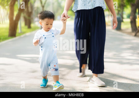 Asian mother walks with her child holding his hand in the spring park. Responsible parenting concept - Stock Photo